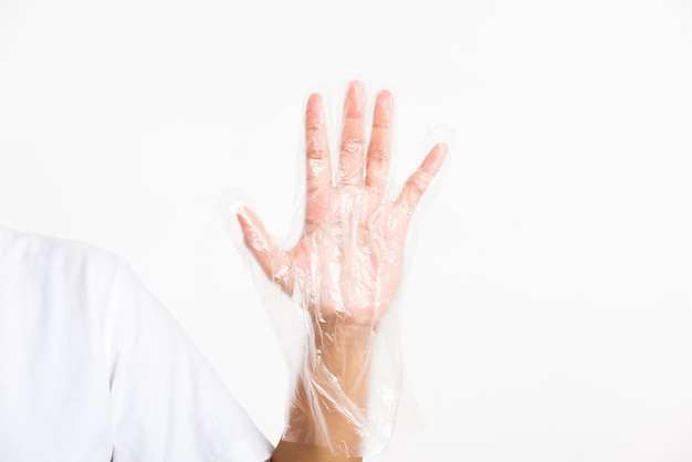 Woman hand wearing single use protect disposable transparent plastic glove