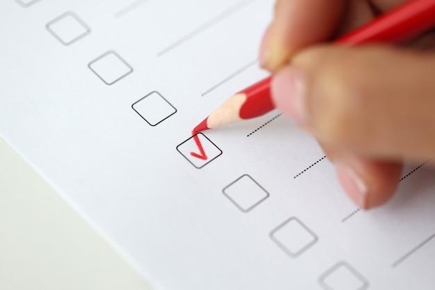 여자 손은 설문지 개념을 통과하는 테스트에서 빨간색 체크 표시로 답변을 표시합니다.