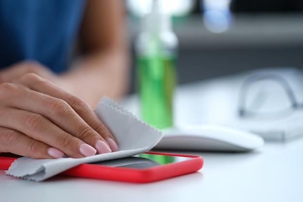 消毒ナプキンのクローズアップで携帯電話の画面を拭く女性
