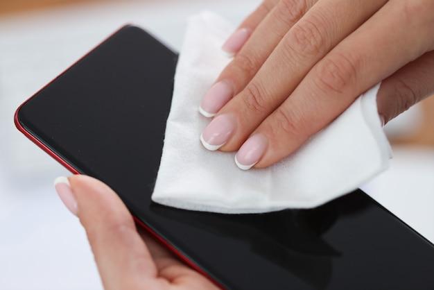 湿った布のクローズ アップで携帯電話の画面を拭く女性の手