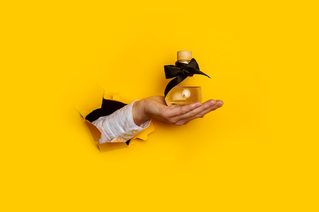 引き裂かれた穴にオイル香水のボトルを持つ女性の手