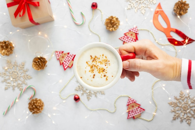 Женская рука с чашкой капучино против рождественских украшений. вид сверху