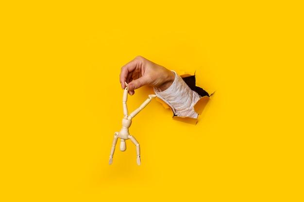 引き裂かれた穴に逆さまに脚で木製の男と女性の手