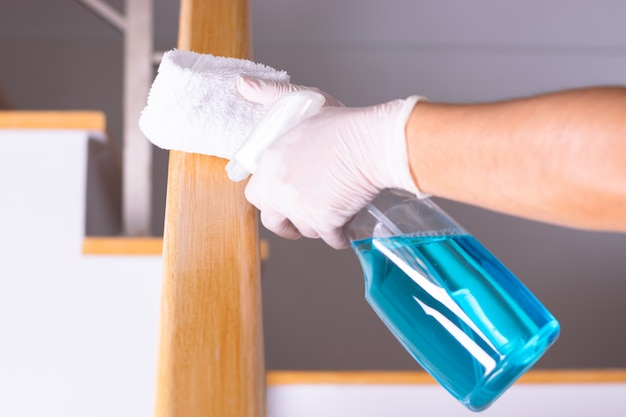 Woman hand with alcohol,disinfectant spray on wipes of banister in home for safety
