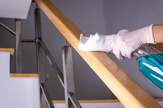 Woman hand with alcohol, disinfectant spray on wipes of banister in home