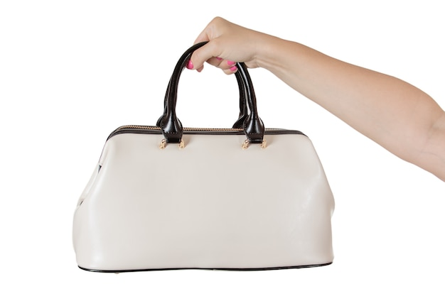Woman hand with cream coloured leather handbag on a white background.