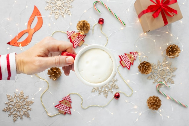Woman hand with a cup of cappuccino against christmas decorations background.