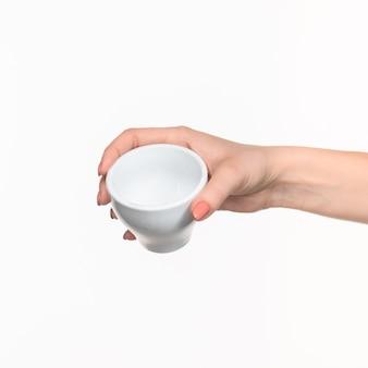白い背景の上にカップを持つ女性の手