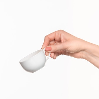 Mano della donna con la tazza su bianco