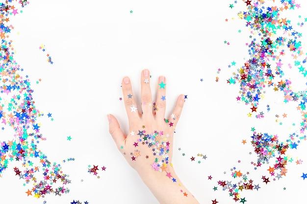 Woman hand with festive color star confetti