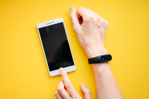 Woman hand with fitness tracker and smartphone on a yellow