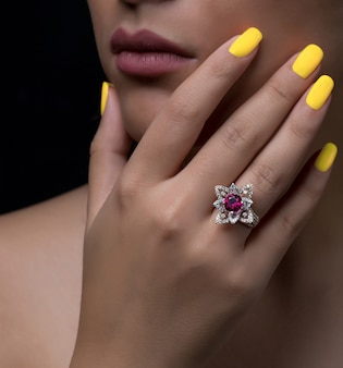 Woman hand with flower-shaped diamond ring with white and burgundy stone