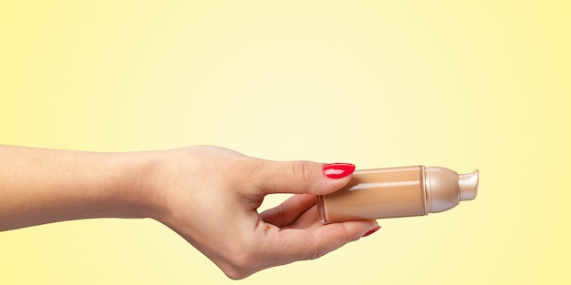 Woman hand with a foundation cosmetic tool isolated on color background