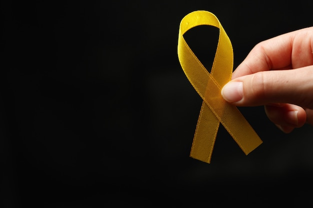 Woman hand with gold ribbon on dark background