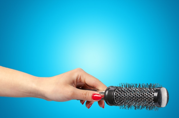 Woman hand with a hair comb isolated on a blue