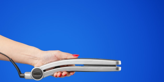 Woman hand with a hair iron isolated on a color background