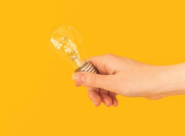 導かれた電球、オレンジ色または黄色の孤立した背景の上の導かれたランプを持つ女性の手