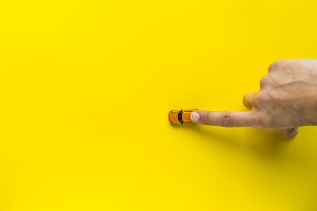 Woman hand with little yellow toy car on a yellow background