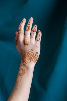 Woman hand with mehndi near blue textile