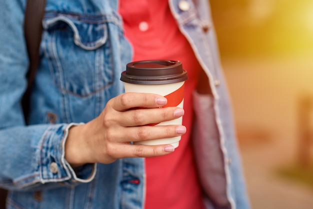 Woman hand with paper cup of coffee take away in a city street