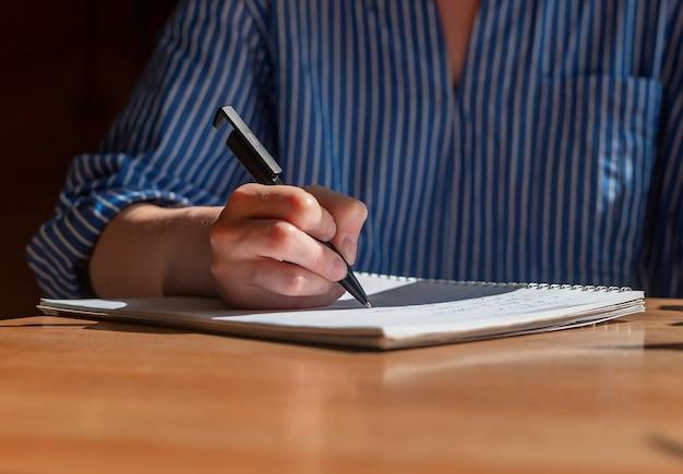 Рука женщины с ручкой писать в блокноте на деревянном столе с солнечным светом крупным планом