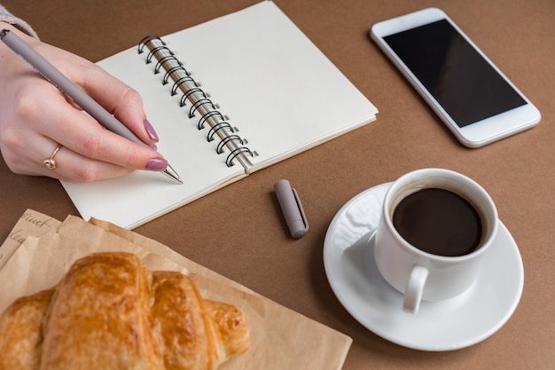 Woman hand with pen writing on notebook at coffee shop. freelancer working in outdoor. coffe break with croissant