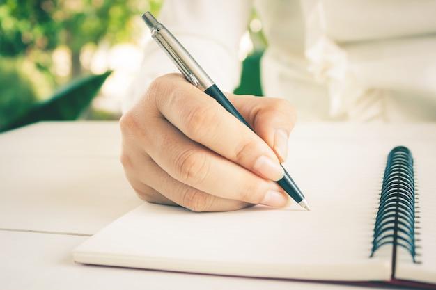 Рука женщины с сочинительством ручки на белой тетради. с копией пространства.
