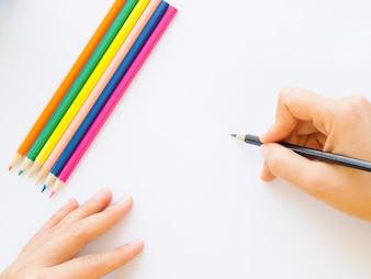 白い紙に鉛筆を書く女性の手。