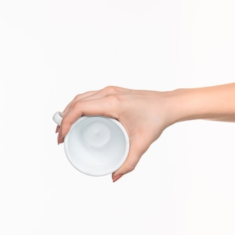 Woman hand with perfect white cup on white