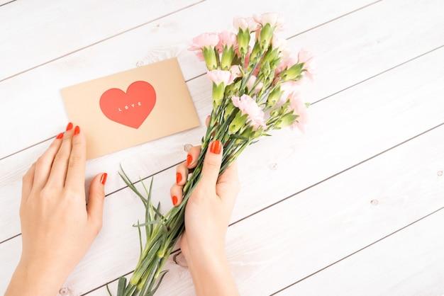 赤い爪を持つ女性の手はラブレターを保持します。