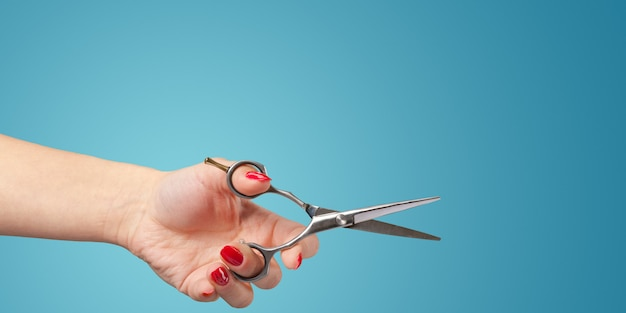 Woman hand with  scissors isolated on blue