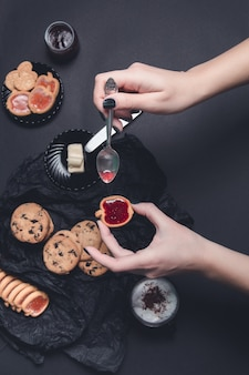 Woman hand with spoon with jam and biscuits near cup of coffee or cappuccino and chocolate cookies on black table background.