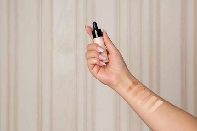 메이크업 베이스가 있는 유리병을 들고 있는 메이크업 파운데이션 견본을 들고 있는 여성의 손. 텍스트를 위한 공간