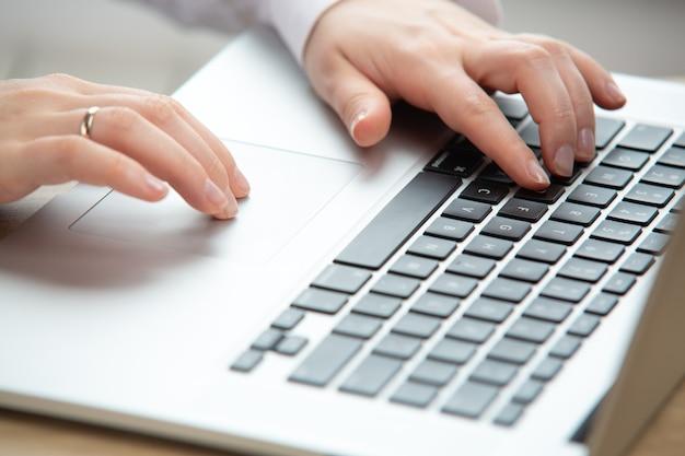 터치패드를 사용하여 노트북 작업을 하는 여성 손 검역 중 집에서 작업