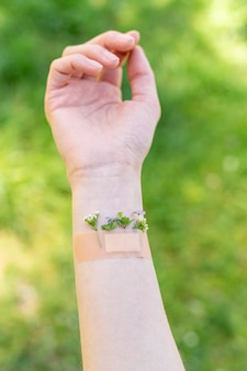 Woman hand woth flowers and band-aid