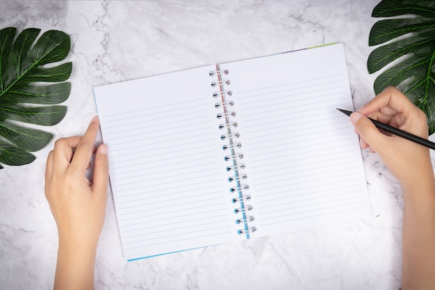 Woman hand writing in a blank white page notebook on white marble desk