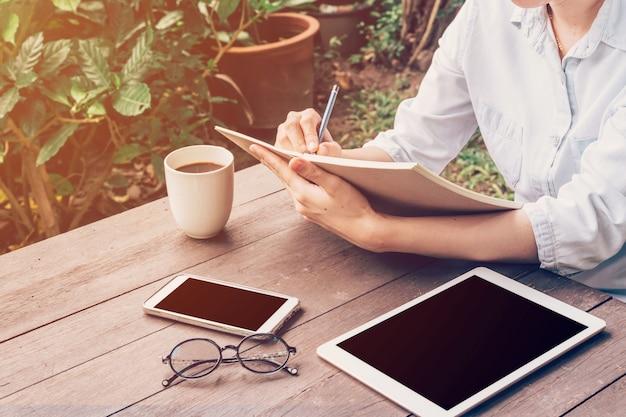 Женщина руки, писать книгу и телефон, таблетка на столе в саду в кафе с урожай тонированное.