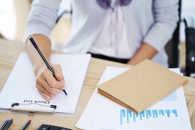 Woman hand writing check list paper, memo planning concept. paperwork for filling in information in business.