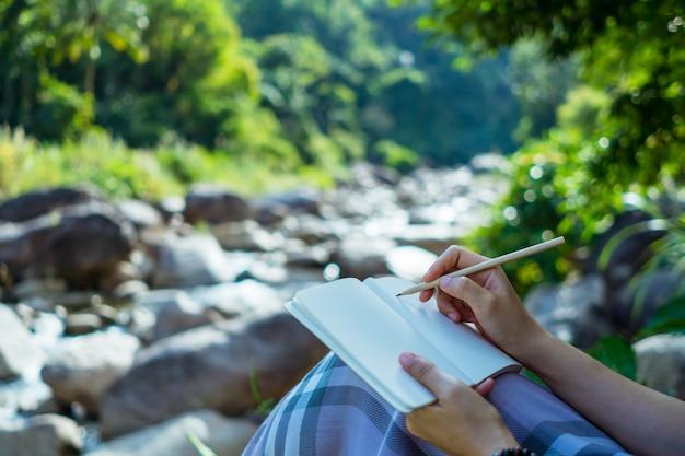 여자 손 작은 흰색 메모 노트에 적어 잊어 버리거나 계획을 세우지 않도록 메모하십시오.