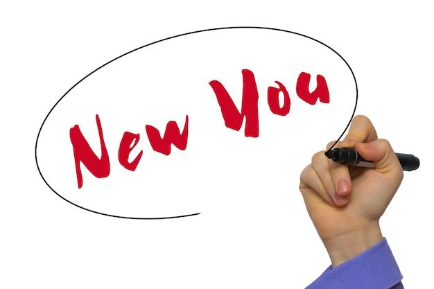 白い背景の上に分離されたマーカーで空白の透明なボードに新しいあなたを書く女性の手。ビジネスコンセプト。ストック写真