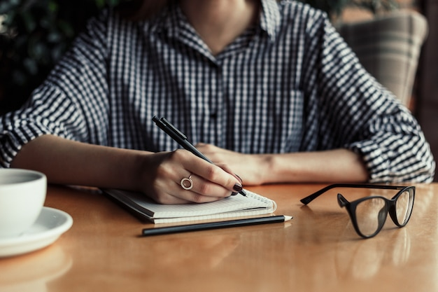 Woman hand writing note pad on wood table in coffee shop