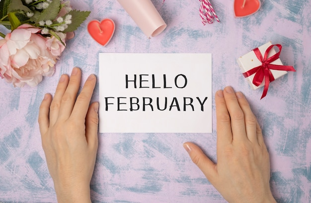Woman hand writing a note on a paper. handwritten text hello february, motivation concept