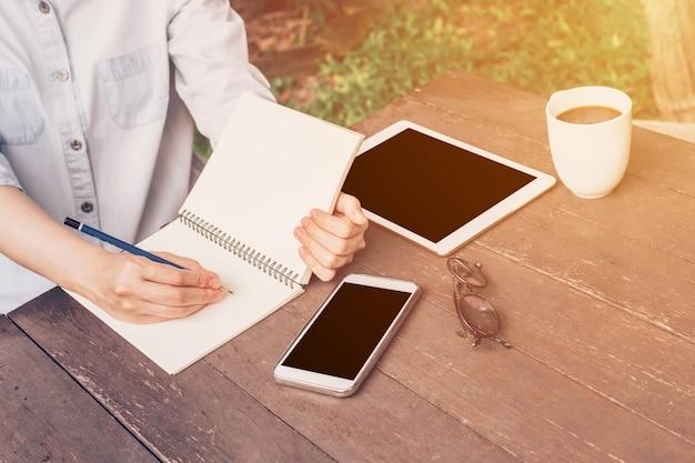 Женщина рука, писать ноутбук и телефон, таблетка на столе в саду в кафе с урожай тонированное.