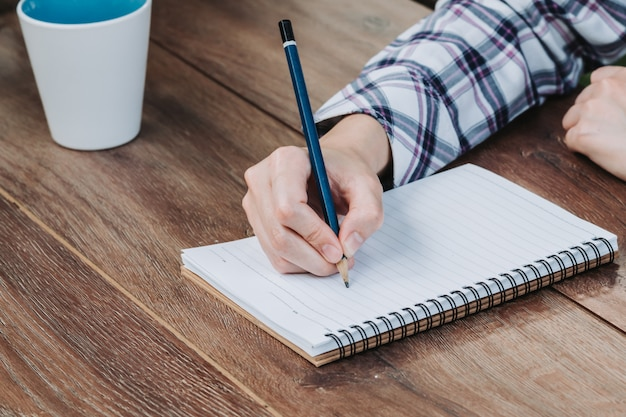 Woman hand writing notepad and holding phone on wooden table at coffee shop