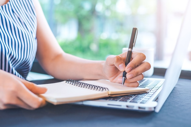 Woman hand writing on notepad with a pen in the office