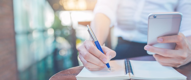 Woman hand writing on a notepad with a pen and using a mobile phone in the office.