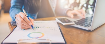 Woman hand writing on charts and graphs that show results with a pen. Web banner.