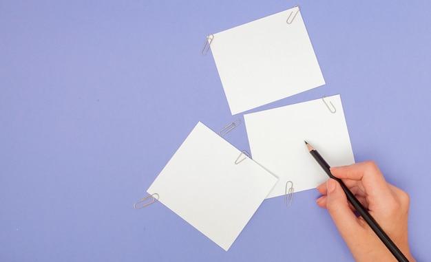 紫のメモ用紙に書く女性の手