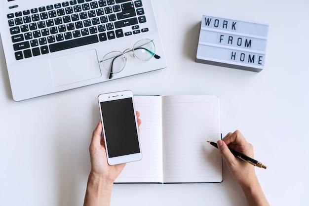 机の上のスマートフォンを使用しながらノートに手書きの女性