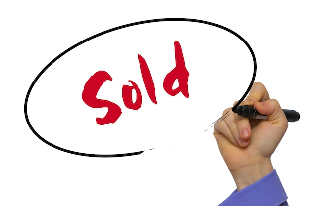 Woman hand writing sold on blank transparent board with a marker isolated over white background. business concept. stock photo